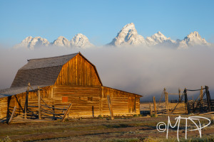 Barn at sunrise as clouds reveal the Grand Tetons; WY
